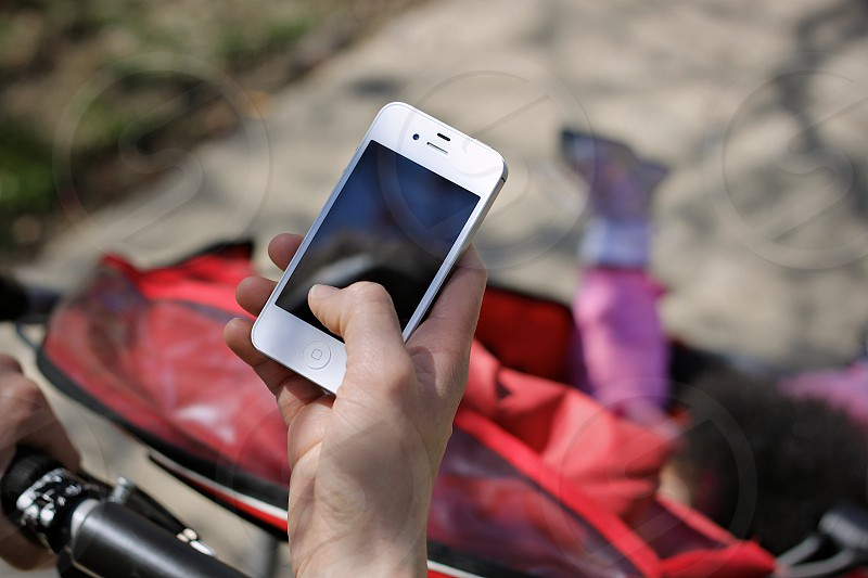 close up of woman holding phone while a pushing stroller photo