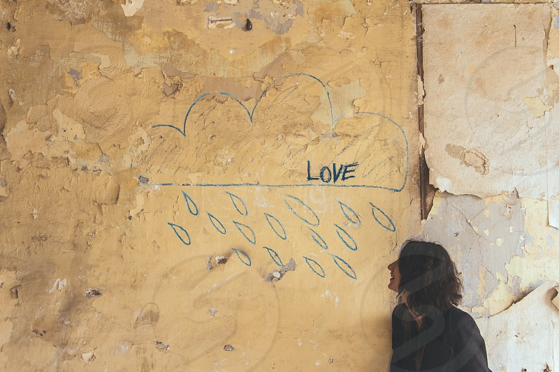 Woman in front of wall depicting a shower of love photo
