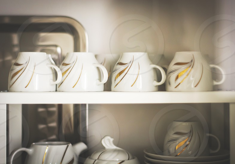 Closeup of white decorated coffee cups in a cupboard photo