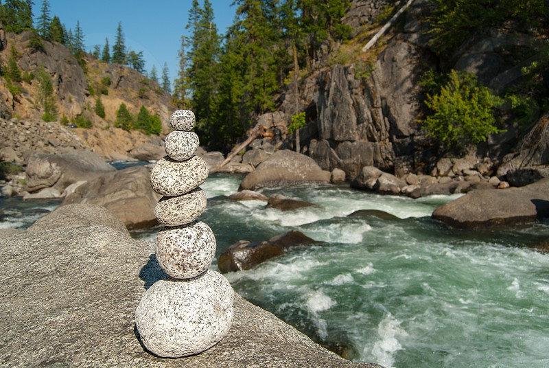 Rock cairn stacking balance river sunshine mountains stream rapids peace harmony blue sky photo