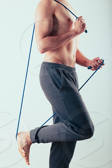 Young man holding skipping rope doing exercises at home. Portrait orientation photo