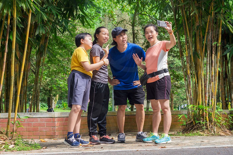Chinese family happily taking selfie photo using smart phone in a China park wearing sportswear photo