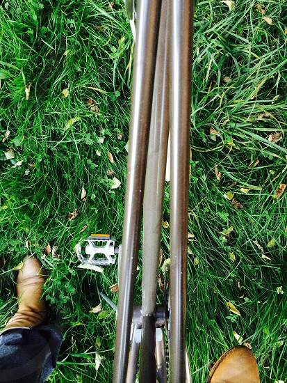 on my handmade vintage heritage bike view over pedals and feet grass wildly and green photo