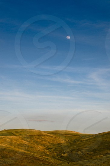 mountain slopes on a bright sunny day with moon on sky photo