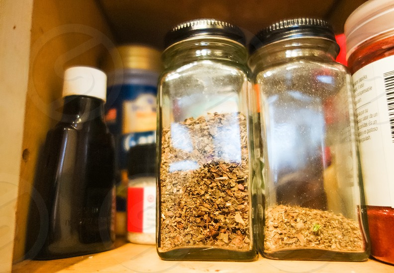 2 clear jars with herbs in shelf photo