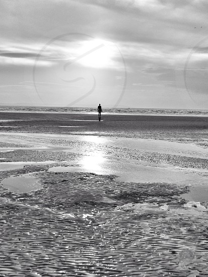 view of person standing by seashore photo