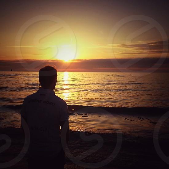 man standing on seashore photograph photo