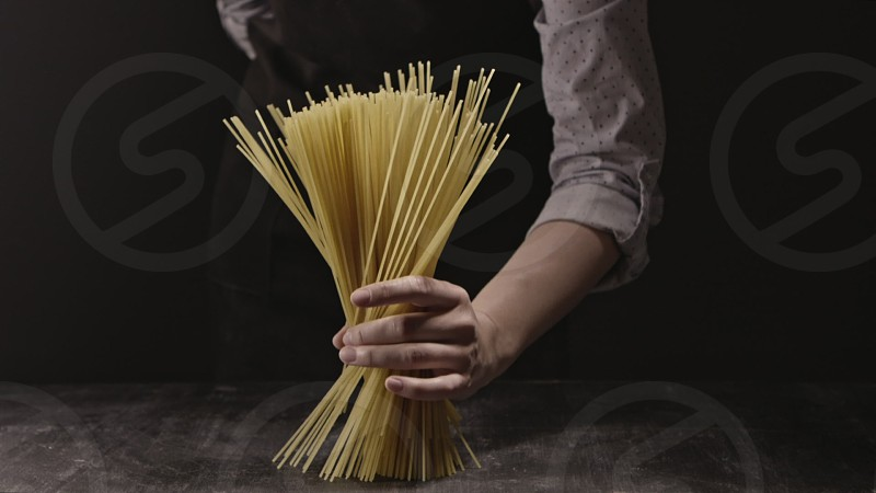 Girl's hand with fresh raw bunch of the pasta on a wooden table. Slow motion Full HD video 240fps 1080p. Concept of italian food and cooking dinner. photo