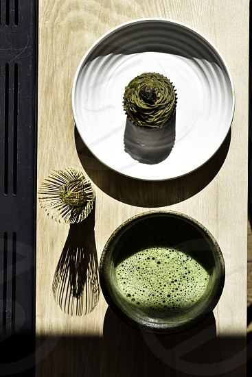 Overhead shot. Green tea on table with a white plate and cake. photo