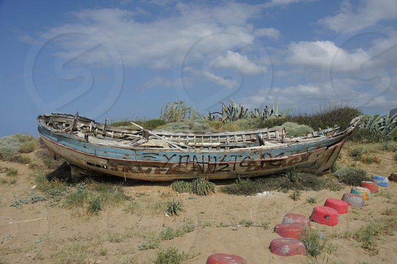 old rotten life craft on empty shore photo