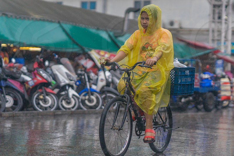 A lady cycling a bicycle in the rain. Taken in Thailand in April. photo