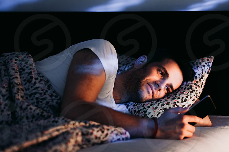Young man using smartphone in bed at night photo