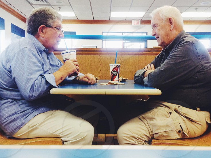 2 men sitting and face to face photo