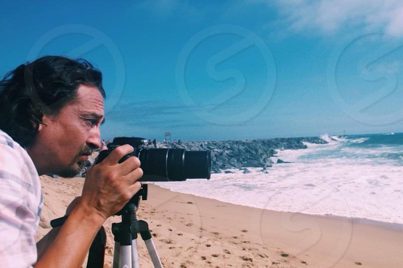 man taking  a picture of the ocean photo