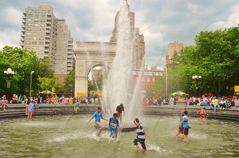 children playing on water fountain photo