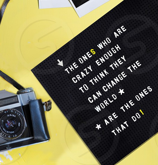 Overhead shot of a camera and noticeboard with inspirational quote. photo