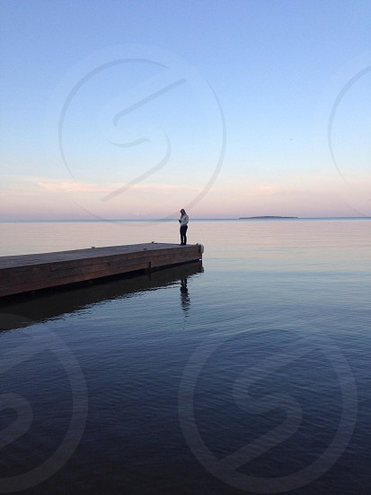 person on dock at lake photo