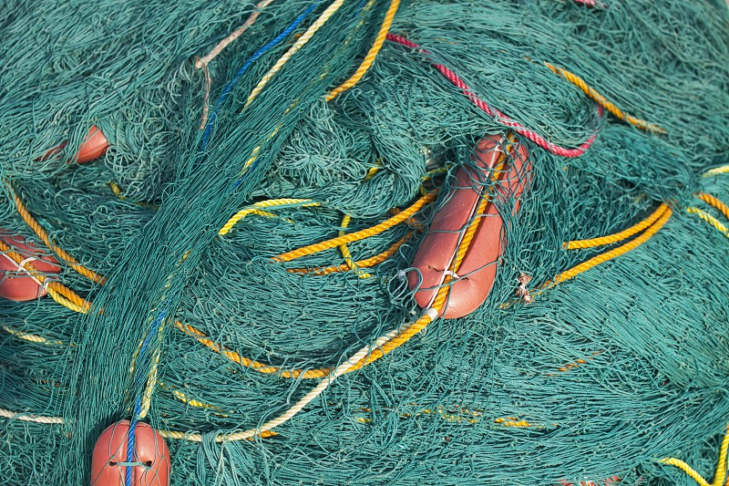 Turquoise fishing nets and yellow ropes with red floats. photo