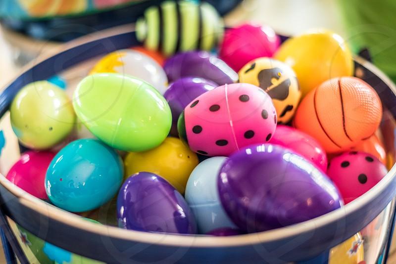 Easter basket full of colorful plastic Easter eggs. photo