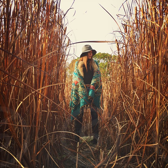 woman in blue red and yellow floral cardigan wearing gray hat beside brown grass field photo