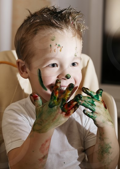 Excited handsome little boy playing with finger paints laughing as he holds up his hands full of colorful paint daubs photo
