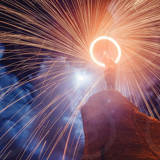 person standing on rocky mountain with lights photo