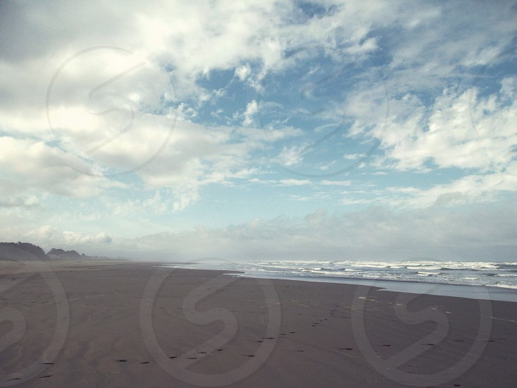 Hazy cludy beach with white cap waves photo