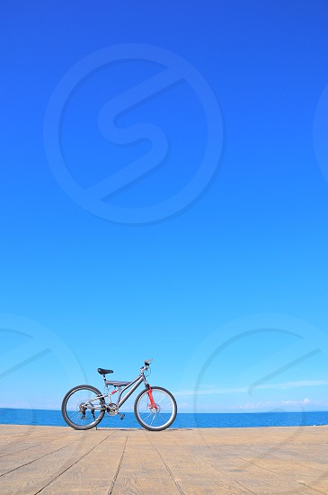 gray full suspension bicycle on brown wooden surface beside wide blue body of water under clear blue sky photo