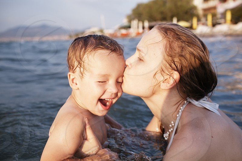 Mother kissing her young child while bathing in the sea waters during sunset photo