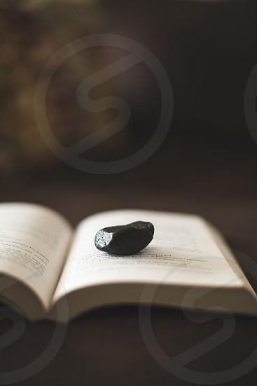 black stone on white book page photo