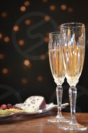 Sparking wine champagne/wine flutes cranberry chèvre cranberries crackers silver tray vintage wood table lights holidays photo