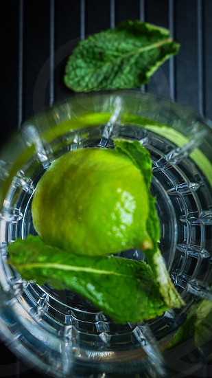 green lemon fruit inside clear glass container placed on black plastic surface photo