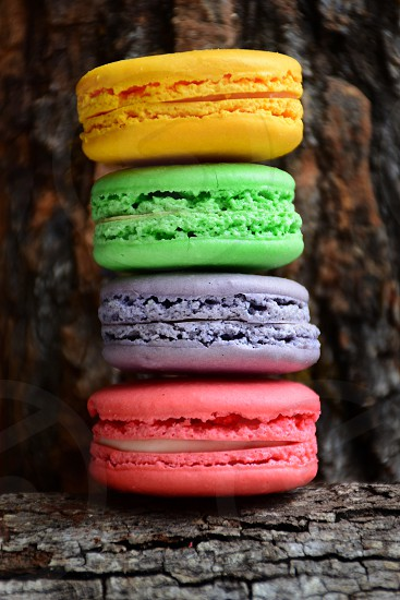 cheese buko pandan taro and strawberry press macaroons piled up together on brown wooden bark during daytime photo