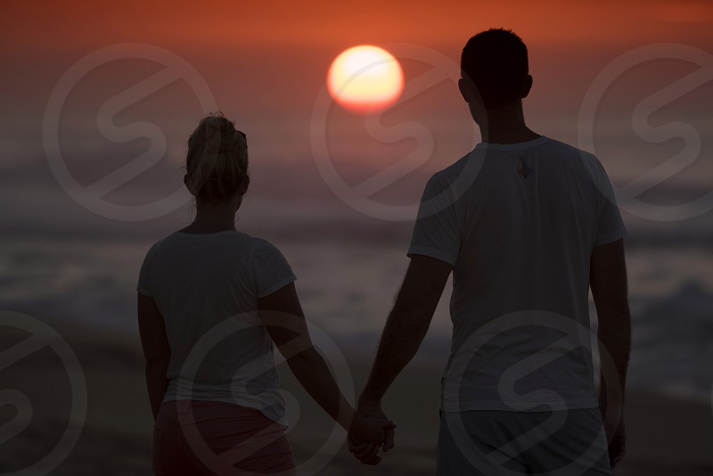 Sunset Hawaii O'ahu north shore beach Pacific Ocean silhouette couple holding hands photo