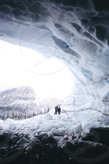 two persons standing at the entrance on snow covered cave photo
