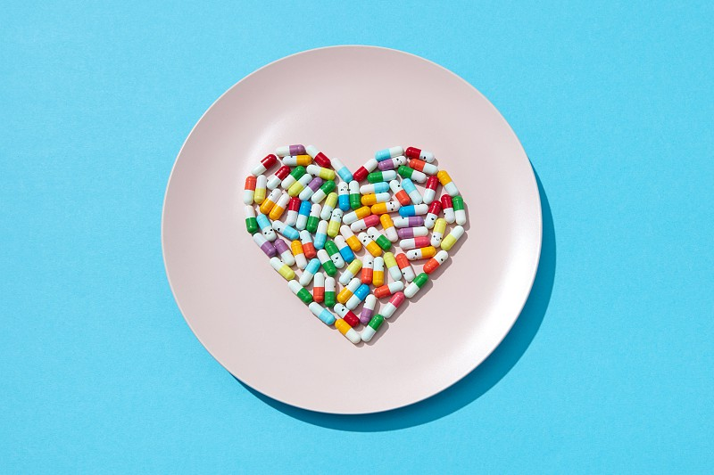Many different pills and supplements in a shape of a heart on a white plate on a blue background. Cardiovascular disease prevention. Flat lay photo