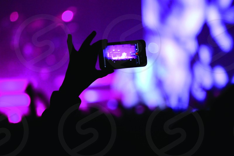 person holding camera inside concert hall photo