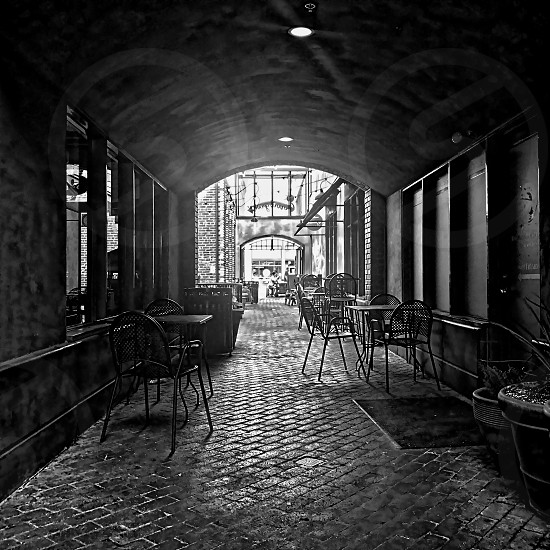 Looking straight down an alley with bistro tables photo