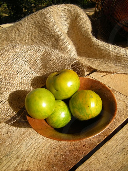 Green tomatoes on wooden table with burlap photo