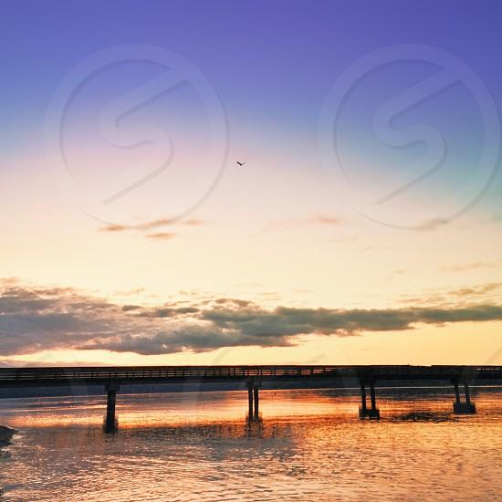 sunset above bridge over ocean water photo