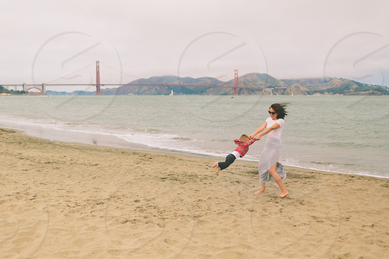 A mother swinging her son on the beach in San Fransisco. photo