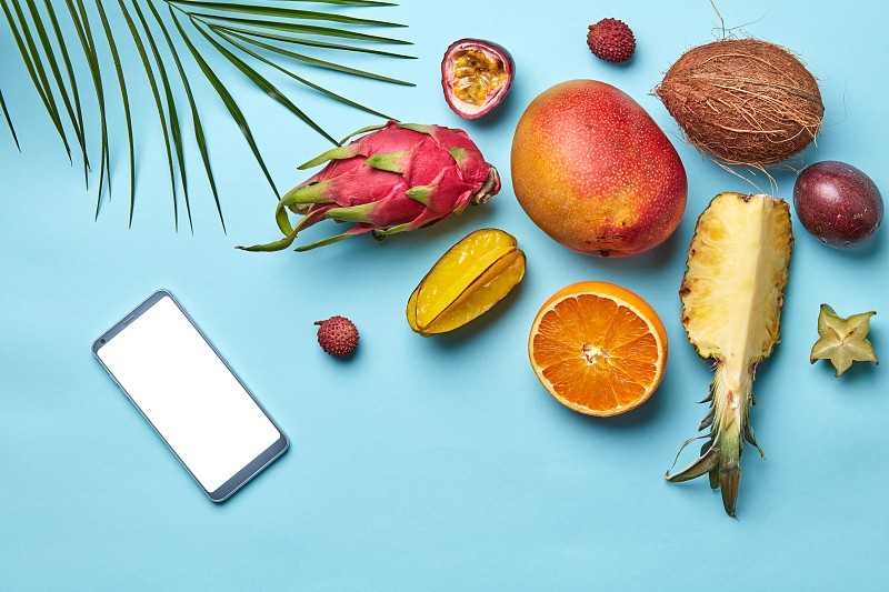 Ripe variety of exotic fruits mobile and palm leaf on a blue background with copy space for text. Modern online shopping. Flat lay photo