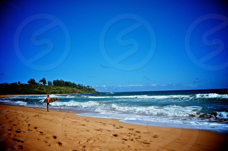 blue ocean waves beige sandy beach surfer carrying board  photo