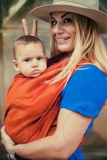 girl young baby child kid mom mother fashion urban smiling smile portrait face goofy hug summer day hat blue orange photo
