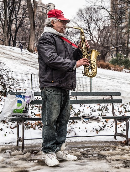 Man playing the saxophone in New York Central Park in snow. photo