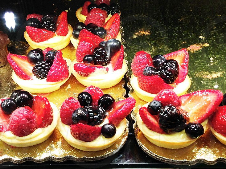 berries on tarts on cooking sheet photo