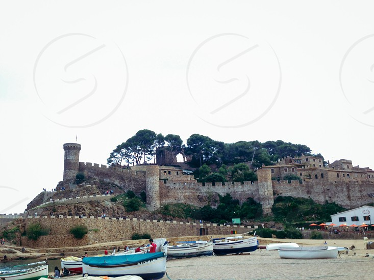 gray castle structure and white and blue boats against clear skies photo