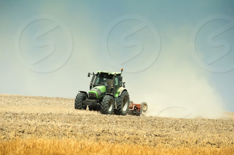Tractor plowing field on blue sky background. photo