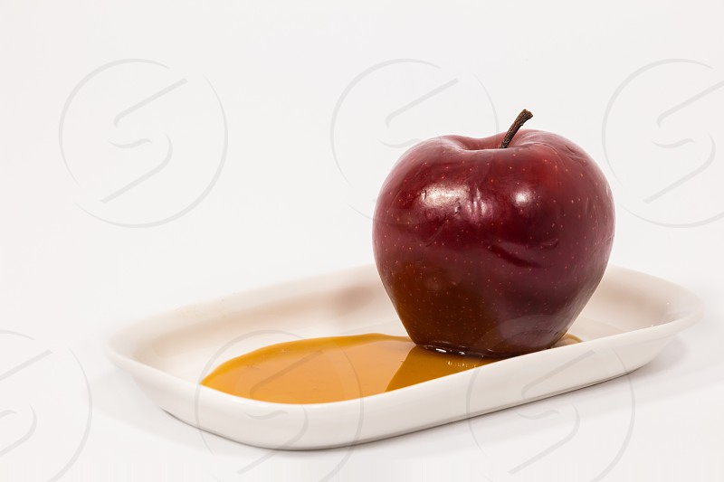 Red apple on white plate with honey isolated on a white background. Symbols of Jewish New Year - Rosh Hashanah.   photo