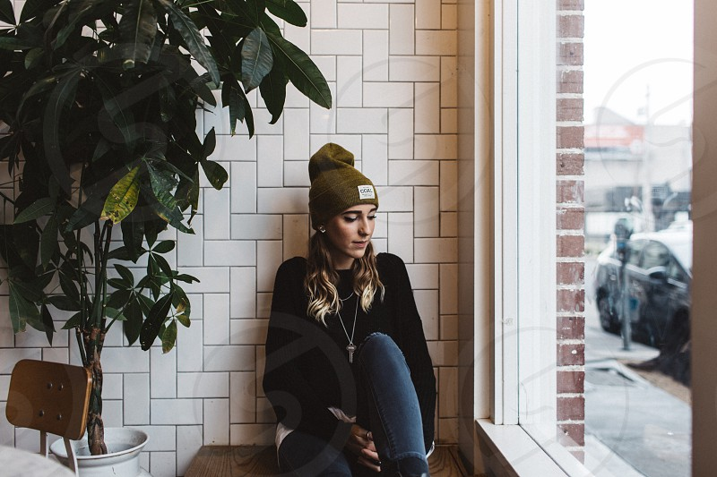 woman in black sweater and blue jeans wearing brown knit cap sitting in front white brick wall between green leaved plant and glass mirror during daytime photo